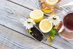 Black tea ceremony - glass full of tea, sugar, yellow lemon, tea leaves, spices on a wooden boards background. Black tea ceremony - glass full of tea, tea leaves stock image