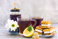 Black tea ceremony - waffles, glass full of tea, glass pot, sugar, yellow lemon, flower, tea leaves, spices on a wooden boards stock image