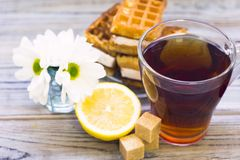 Black tea ceremony - waffles, glass full of tea, glass pot, sugar, yellow lemon, flower, tea leaves, spices on a wooden boards stock photo