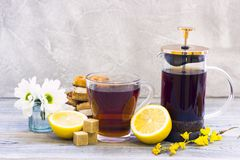Black tea ceremony - waffles, glass full of tea, glass pot, sugar, yellow lemon, flower, tea leaves, spices on a wooden boards stock photos