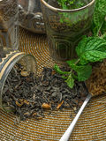 Black tea in a crystal glass, mint leaves, dried tea, brown suga Royalty Free Stock Images