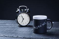 Black tea cup with alarm clock on a table Royalty Free Stock Images
