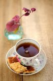 Black tea in a cup with cookies. On wooden background Royalty Free Stock Images