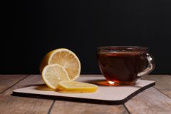 Black tea. Cup of fragrant black tea and segment of a lemon on a black background royalty free stock photo