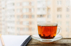 Black tea in cup of glass on the windowsill Royalty Free Stock Image