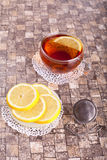 Lemon tea. Black tea in a cup with lemon and strainer Stock Images