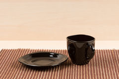 Black tea cup standing near black plate on tablemat. Stock Image