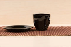 Black tea cup standing near black plate on tablemat. Royalty Free Stock Images