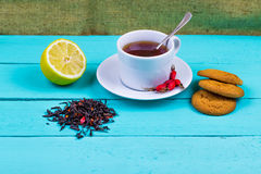 Black tea with a dogrose, a lemon and cookies Royalty Free Stock Images