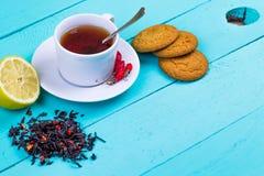 Black tea with a dogrose, a lemon and cookies Stock Photos