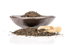Black tea earl grey isolated on white. Lot of pieces of dry black tea earl grey in a grey ceramic bowl with wooden scoop isolated on white background royalty free stock photos