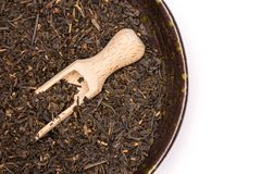 Black tea earl grey isolated on white. Lot of pieces of dry black tea earl grey in a grey ceramic bowl with wooden scoop flatlay isolated on white background royalty free stock image