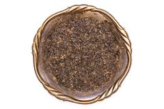Black tea earl grey isolated on white. Lot of pieces of dry black tea earl grey in old iron bowl flatlay isolated on white background royalty free stock photo