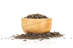 Black tea earl grey isolated on white. Lot of pieces of dry black tea earl grey with wooden bowl isolated on white background royalty free stock image