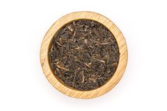 Black tea earl grey isolated on white. Lot of pieces of dry black tea earl grey with wooden bowl flatlay isolated on white background stock photography