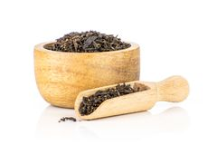 Black tea earl grey isolated on white. Lot of pieces of dry black tea earl grey with wooden bowl and wooden scoop isolated on white background royalty free stock images
