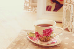 Black tea in elegant vintage porcelain cup on wooden table Royalty Free Stock Image
