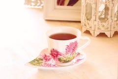 Black tea in elegant vintage porcelain cup on wooden table Stock Images