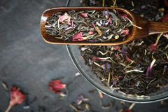 Black tea with flower  petals in the wooden spoon top view Royalty Free Stock Photography