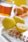 Black tea with fresh lemons and flu pills in blister with thermo Stock Image