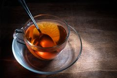 Black tea freshly brewed in a glass cup and a spoon on a dark ru. Stic wooden table, steaming hot drink against cold and flu, creative lightning, copy space Stock Images