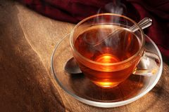 Black tea freshly brewed in a glass cup, steaming hot drink on d Stock Photos
