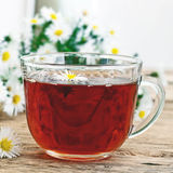 Black tea in a glass cup and chamomile flowers Stock Images
