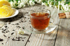 Black tea in a glass cup and saucer. Black tea with lemon and cinnamon in a glass cup and saucer on a wooden table. Next to a cup of black tea are flowers Stock Image