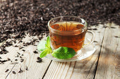 Black tea. In a glass cup and saucer on a wooden table. Next to a cup of  scattered dry tea Royalty Free Stock Images