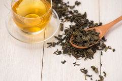 Black tea in a glass cup and tea leaves in wooden spoon on black. Stone background Royalty Free Stock Images