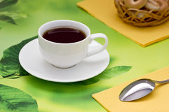 Black tea on a green background. In the yellow napkins Stock Photos