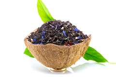Black tea with green leaf in coconut rind isolated on white.  royalty free stock image