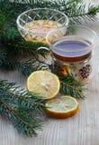 Black tea, honey, lemon slices  on old wooden board, fir tree ar Stock Image