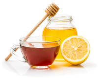 Black tea, honey and  lemon. Black tea in a transparent glass cup honey pot and spoon for honey, lemon closeup isolated on a white background Royalty Free Stock Image