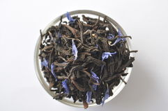 Black tea leaves with blue flower petals in a bowl. Isolated on white. Stock Images