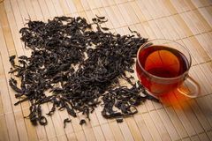 Black tea leaves and cup Royalty Free Stock Photos