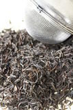 Black tea leaves with tea strainer Stock Photo