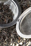 Black tea leaves with tea strainer Stock Photos