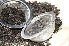 Black tea leaves with tea strainer Stock Image
