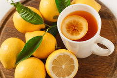 Black tea with lemon closeup. Black tea with lemon on a wooden board, closeup Royalty Free Stock Image