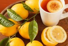 Black tea with lemon closeup. Black tea with lemon on a wooden board, closeup Stock Photo