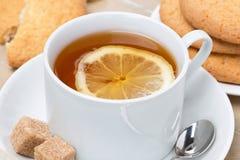 Black tea with lemon and cookies, close-up Stock Photos