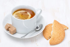 Black tea with lemon and cookies on white wooden table Royalty Free Stock Photography