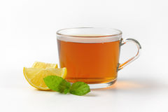 Black tea with lemon. Cup of black tea with lemon on white background Royalty Free Stock Image