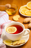 Black tea with lemon, ginger and honey on the wooden table. Stock Image
