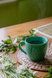 Black tea with lemon in green mug with snowdrops background Stock Photo