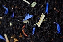 Black tea with lemon peel and flower petals. View Royalty Free Stock Photos