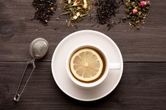 Black tea with lemon and several views of tea on a wooden background stock photo