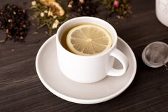 Black tea with lemon and several views of tea on a wooden background royalty free stock photo