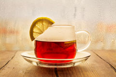 Black tea with lemon slices in a glass cup Stock Images